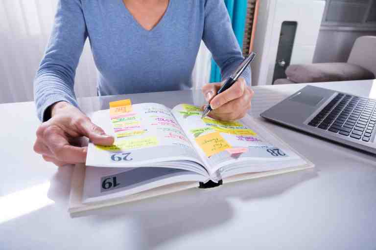 woman writing in one of the best planners for moms