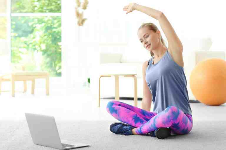 woman stretching while following a workout online