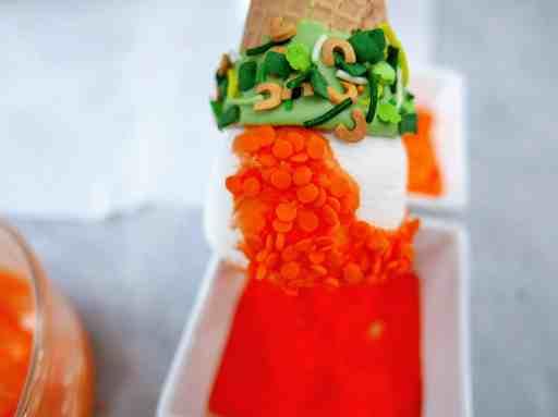 adding orange sprinkles to the orange candy coating