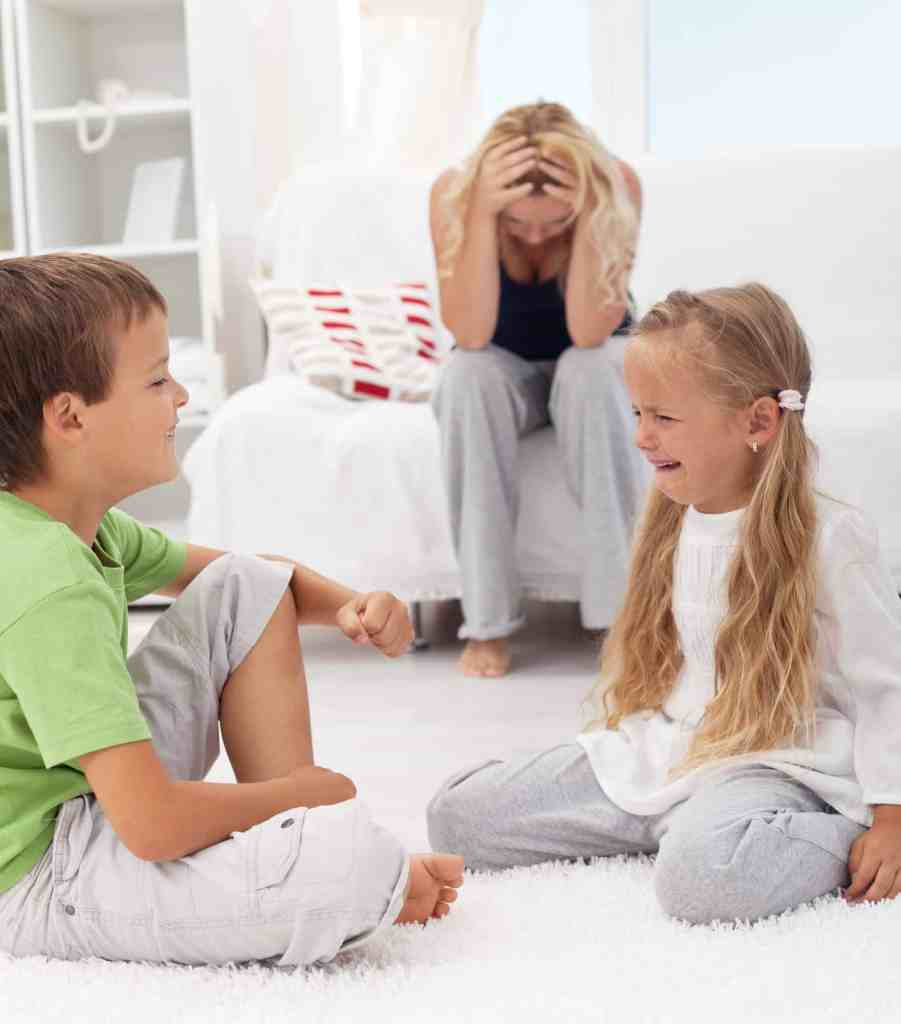 Exasperated mom sitting on couch while little boy and girl fight and cry