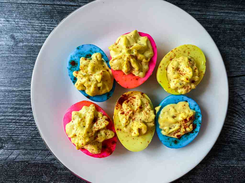 yellow, blue and pink colored deviled eggs on a plate
