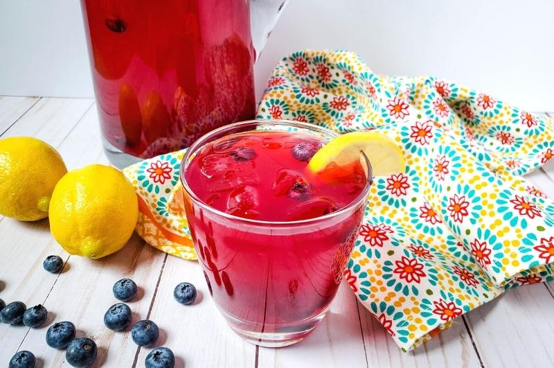 glass of blueberry lemonade with lemons and blueberries