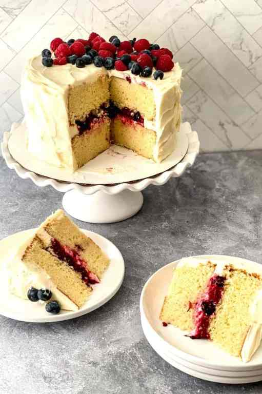 berry Chantilly cake on platter with slices on plates