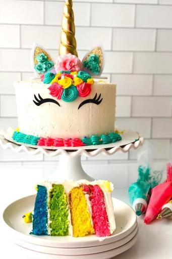 Rainbow unicorn cake with a cut slice on a plate