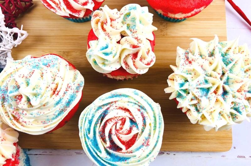 red, white, and blue cupcakes on a wood tray