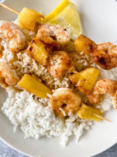 grilled honey garlic shrimp skewers on a bed of rice