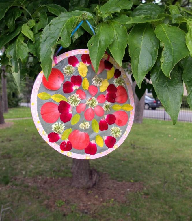 DIY nature mandala craft hanging in a tree