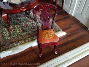 Doll house chair with EGA logo embroidered into seat cushion