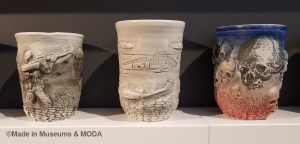 Close-up of the ceramic cups featuring the artist's military experiences