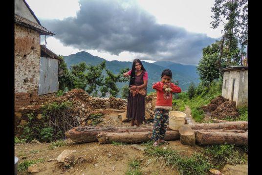 Fantômes du passé. Les femmes népalaises ont pour habitude de se brosser les cheveux sur le seuil de leur maison. Cette habitude n'a pas changé malgré la destruction de leur habitat.