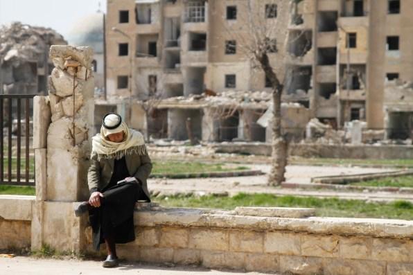 Un homme lit un livre dans le quartier ravagé d'Hanano. Derrière lui, des ruines.