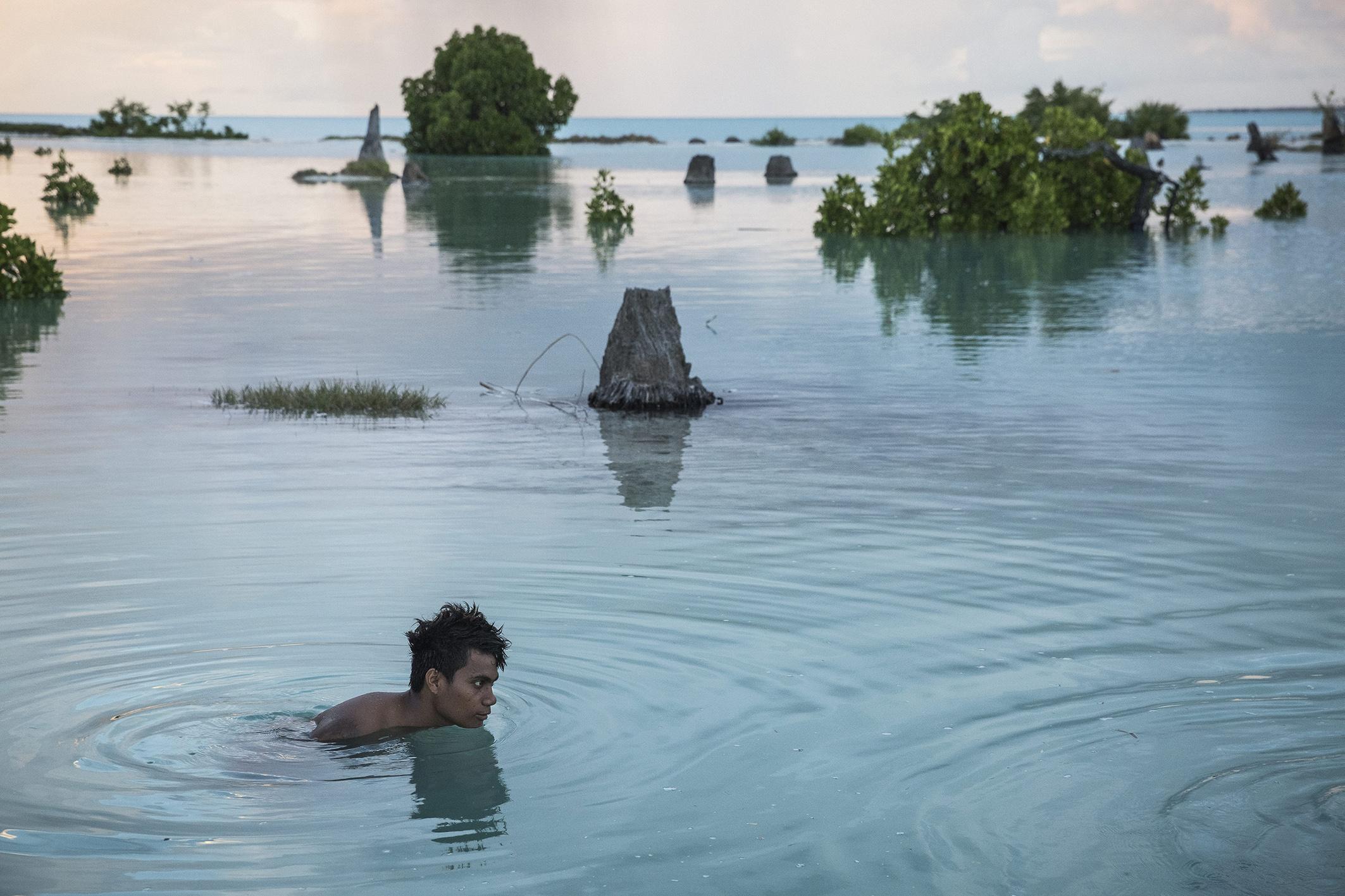 """Peia Kararaua (16 ans), dans un quartier inondé du village d'Aberao, îles Kiribati, l'un des pays les plus durement touchés par la montée du niveau des mers. © Vlad Sokhin / Cosmos / Panos Pictures / laif Peia Kararaua (16) in a flooded part of the village of Aberao, Kiribati, one of the countries most affected by rising sea levels. © Vlad Sokhin / Cosmos / Panos Pictures / laif Photo libre de droit uniquement dans le cadre de la promotion de la 29e édition du Festival International du Photojournalisme """"Visa pour l'Image - Perpignan"""" 2017 au format 1/4 de page maximum. Résolution maximale pour publication multimédia : 72 dpi Mention du copyright obligatoire. The photos provided here are copyright but may be used royalty-free for press presentation and promotion of the 29th International Festival of Photojournalism Visa pour l'Image - Perpignan 2017. Maximum size printed: quarter pageMaximum resolution for online publication: 72 dpi Copyright and photo credits (listed with captions) must be printed."""