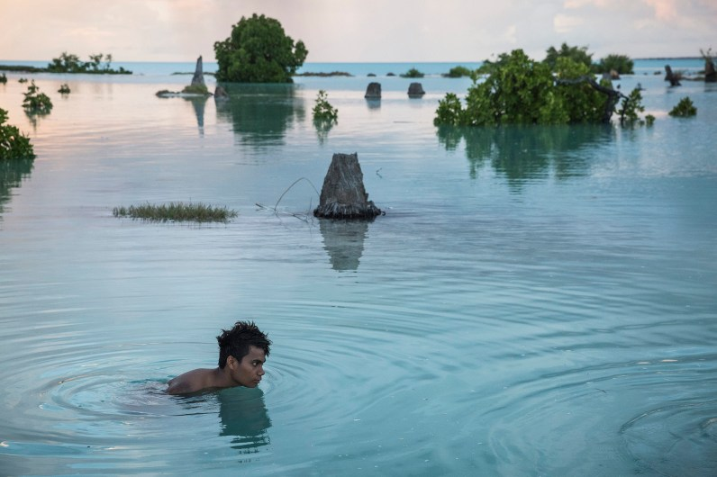 "Peia Kararaua (16 ans), dans un quartier inondé du village d'Aberao, îles Kiribati, l'un des pays les plus durement touchés par la montée du niveau des mers. © Vlad Sokhin / Cosmos / Panos Pictures / laif Peia Kararaua (16) in a flooded part of the village of Aberao, Kiribati, one of the countries most affected by rising sea levels. © Vlad Sokhin / Cosmos / Panos Pictures / laif Photo libre de droit uniquement dans le cadre de la promotion de la 29e édition du Festival International du Photojournalisme ""Visa pour l'Image - Perpignan"" 2017 au format 1/4 de page maximum. 