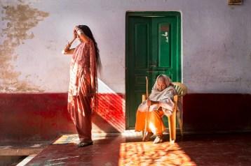 """À l'entrée de l'ashram pour veuves Meera Sehbhagini Mahila, géré par les autorités publiques avec le soutien de Sulabh International : Ranjana (à gauche) et Lalita (à droite), toutes deux veuves de différentes générations. Vrindavan, Uttar Pradesh, Inde, 2013. © Amy Toensing / National Geographic Magazine / National Geographic Creative At the entrance to Meera Sehbhagini Mahila Ashram, a government-run ashram for widows, supported by Sulabh International. Ranjana (left) and Lalita (right) exemplify the changing generations of widows in India. Vrindavan, Uttar Pradesh, India, 2013. © Amy Toensing / National Geographic Magazine / National Geographic Creative Photo libre de droit uniquement dans le cadre de la promotion de la 29e édition du Festival International du Photojournalisme """"Visa pour l'Image - Perpignan"""" 2017 au format 1/4 de page maximum. Résolution maximale pour publication multimédia : 72 dpi Mention du copyright obligatoire. The photos provided here are copyright but may be used royalty-free for press presentation and promotion of the 29th International Festival of Photojournalism Visa pour l'Image - Perpignan 2017. Maximum size printed: quarter pageMaximum resolution for online publication: 72 dpi Copyright and photo credits (listed with captions) must be printed."""