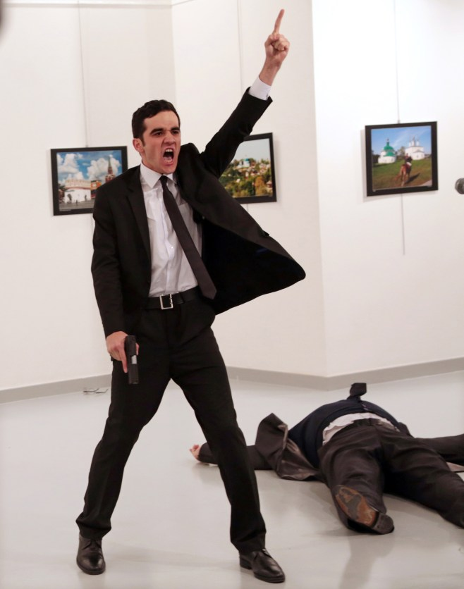 Mevlut Mert Altintas shouts after shooting Andrei Karlov, right, the Russian ambassador to Turkey, at an art gallery in Ankara, Turkey, Monday, Dec. 19, 2016. At first, AP photographer Burhan Ozbilici thought it was a theatrical stunt when a man in a dark suit and tie pulled out a gun during the photography exhibition. The man then opened fire, killing Karlov. (AP Photo/Burhan Ozbilici)