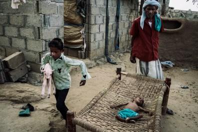 """Saleh Abdo Ahmed et son fils Abdo Saleh chez eux, dans le village d'Al-Jarb. Abdo (3 ans) souffre de malnutrition sévère et risque de mourir. Quelques jours auparavant, sa mère est partie car son mari refusait d'emmener leur enfant dans une clinique. Aslam, Yémen, 7 décembre 2018. Saleh Abdo Ahmed standing near his son Abdo Saleh at home in the village of al-Jarb. Three-year-old Abdo is suffering from severe malnutrition and may die. A few days earlier, Abdo's mother left home because her husband refused to allow the child to be taken to a clinic. Aslam, Yemen, December 7, 2018. © Lorenzo Tugnoli / The Washington Post / Contrasto Photo libre de droit uniquement dans le cadre de la promotion de la 31e édition du Festival International du Photojournalisme """"Visa pour l'Image - Perpignan"""" 2019 au format 1/4 de page maximum. Résolution maximale pour publication multimédia : 72 dpi Mention du copyright obligatoire. The photos provided here are copyright but may be used royalty-free for press presentation and promotion of the 31th International Festival of Photojournalism Visa pour l'Image - Perpignan 2019."""