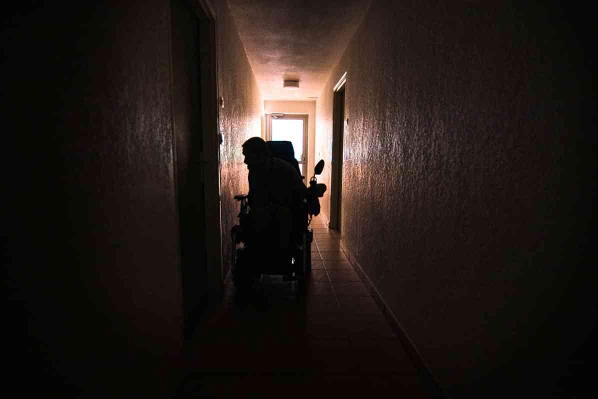 Christophe Riti sur son fauteuil roulant dans le couloir de son immeuble. Photographie de Stephane Ferrer Yulianti.