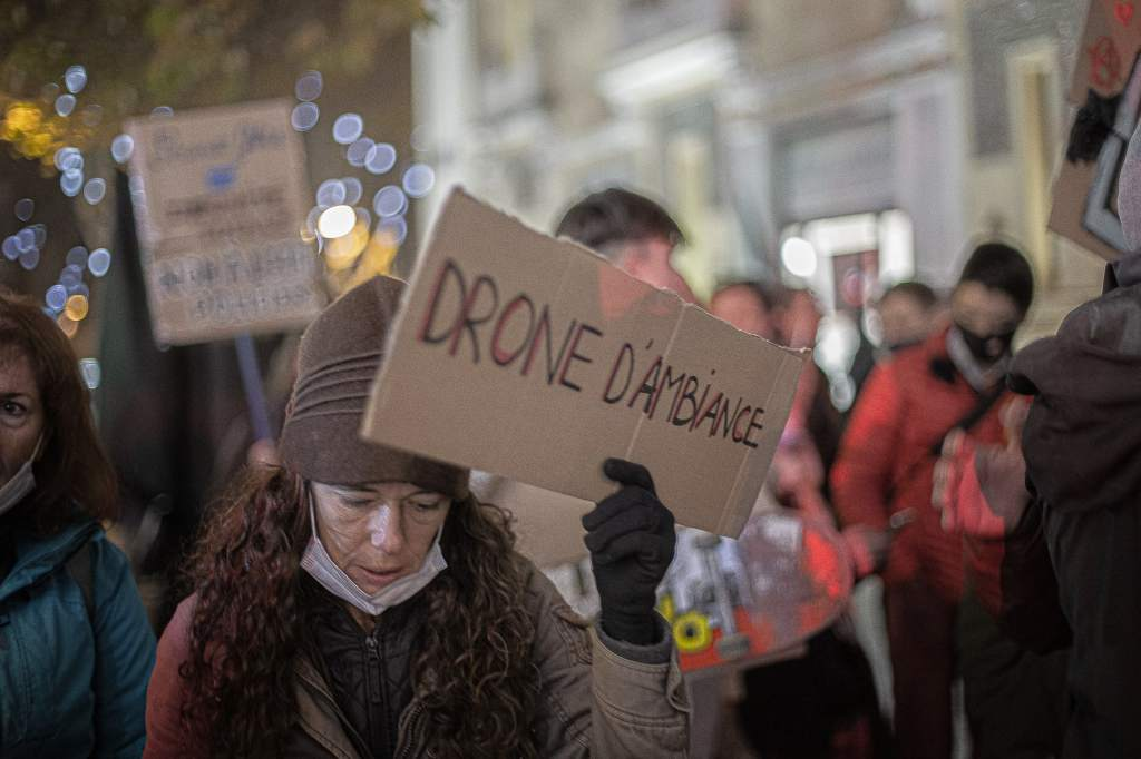 Une manifestante lors de la Marche des Libertes contre la loi Securite Globale porte une pancarte avec le message humoristique drone d ambiance. Perpignan, France. Le 3 decembre 2020. Photographie de Idhir Baha / Hans Lucas.