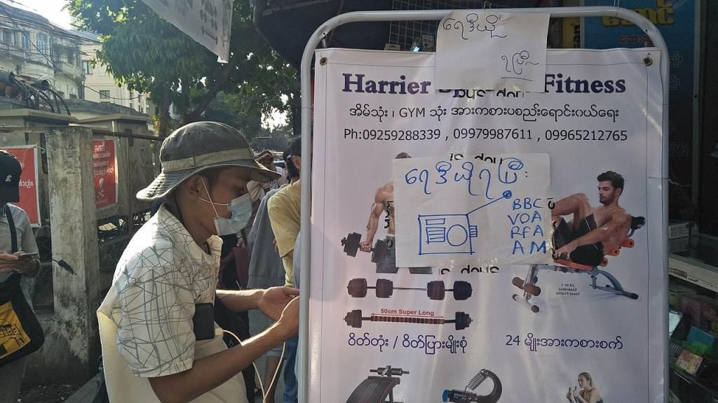 """Pendant la panne continue d'Internet et des médias, beaucoup sont passés à la radio pour obtenir des nouvelles. Un panneau birman manuscrit indique """"Les radios sont maintenant disponibles"""", avec les acronymes de plusieurs grandes stations de radio internationales, dont la BBC, VOA et RFA. © Han Sann"""