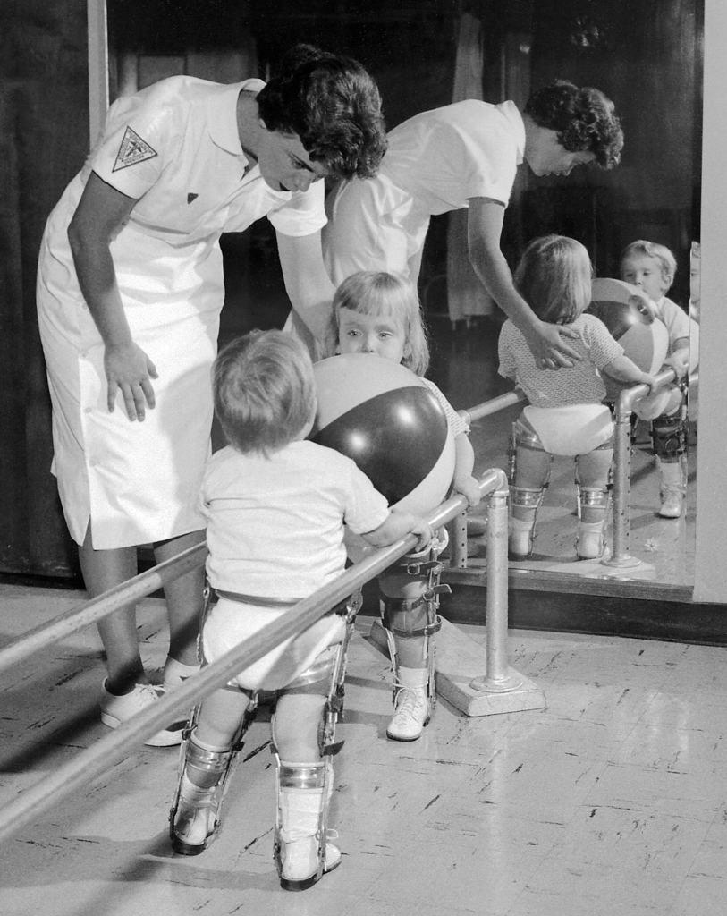 Ce kinésithérapeute aide deux enfants atteints de polio à se tenir à un rail pendant qu'ils exercent leurs membres inférieurs. © CDC PHIL