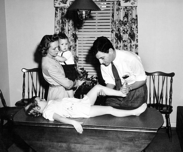 Un agent de l'Epidemic Intelligence Service (EIS), effectuant un test d'évaluation du tonus musculaire sur cette jeune patiente, afin de déterminer si la jeune fille avait subi des effets paralytiques, suite à une infection par la polio. © CDC PHIL