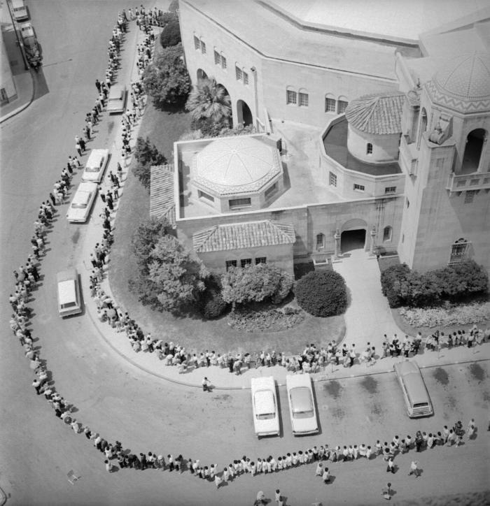 Cette image historique de 1962 montre une vue aérienne d'une longue file de personnes qui attendaient d'être vaccinées contre la polio. La file était si longue qu'elle entourait un auditorium de la ville de San Antonio, au Texas. © CDC PHIL