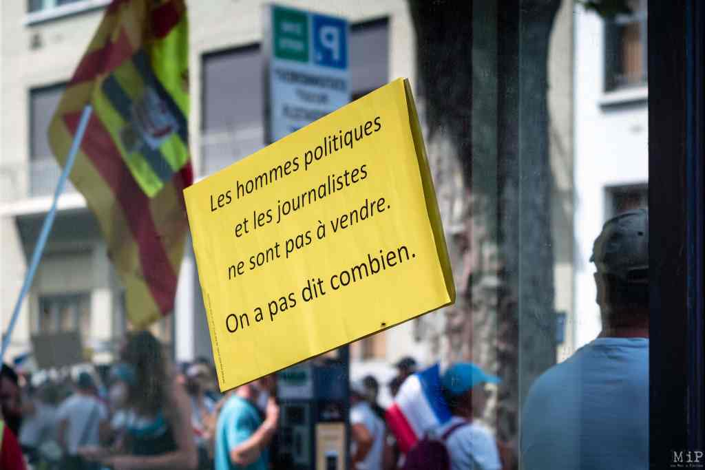 """France, Perpignan, 2021-08-07. Illustration, among the anti-sanitary pass protesters, some of them gathered in front of the headquarters of the newspaper l Independant, with cries of «Collabos"""" or """"liars"""". The newspaper s headquarters was smeared with swastikas, anti-media banners and yellow waistcoat posters. Photograph by Arnaud Le Vu / Hans Lucas.France, Perpignan, 2021-08-07. Illustration, Parmi les manifestants anti-pass sanitaire quelques uns ont arrange la foule devant le siege du journal l Independant, aux de cris de """"Collabos"""", """"menteurs"""" ou """"vendus"""". Le siege du journal fut macule de croix gammees, banderoles anti-medias et d affiches gilets jaunes. Photographie de Arnaud Le Vu / Hans Lucas."""