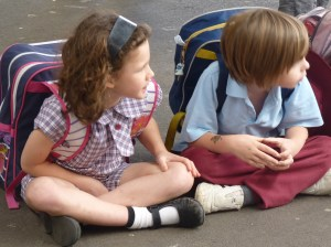 Children sitting in playground with backpacks