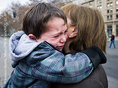 Boy cries in mother's arms. Maybe they have to part.