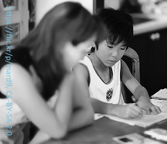 Mother helps her son with homework at kitchen table