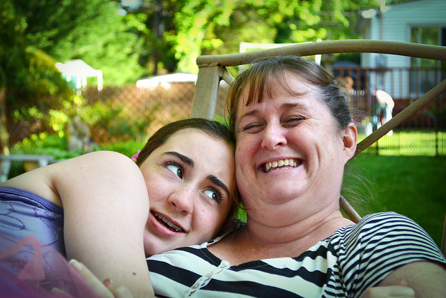 Mother and teen daughter cuddle, enjoying one another