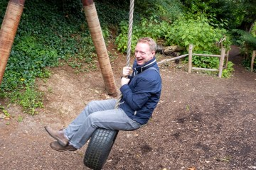 Man plays - swinging on a tyre swing