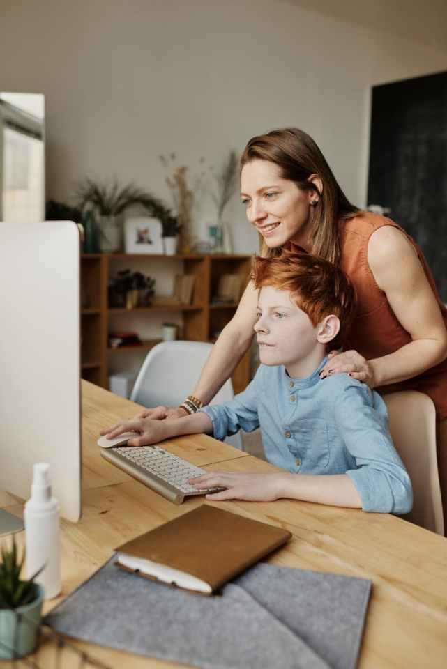 photo of woman and boy looking at computer, teaching her son while smiling