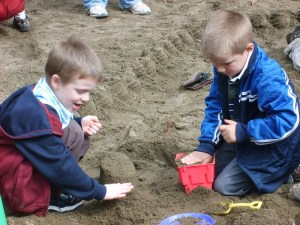 Two young boys play together in a sandpit, very involved in their game together.