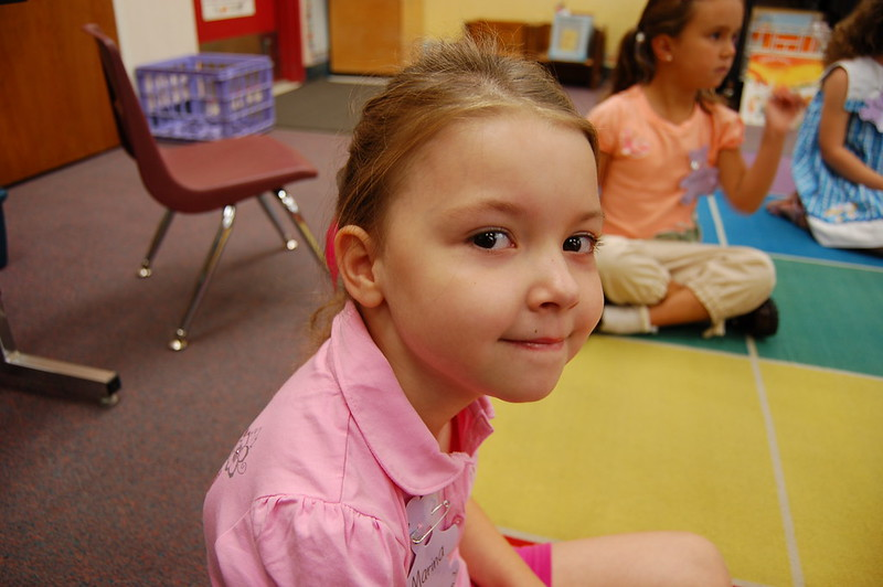 Kindergarten girl sitting on mat in classrooom looks at the camera. She looks happy.