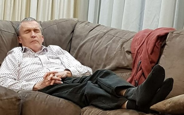 Tired middle aged father falls asleep on a soft couch
