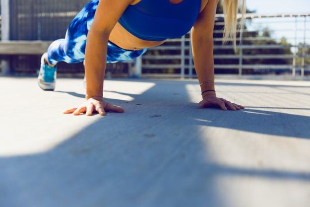 Fit woman doing a plank exercise in blue tights