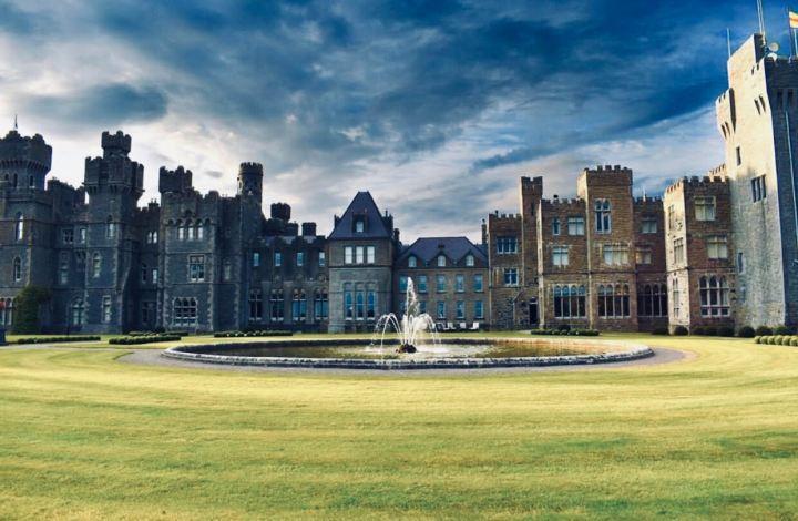 Castelli d'Irlanda: Ashford Castle con la circolare fontana che sorge nel suo giardino. L'immagine frontale fa vedere i suoi diversi stili: il blocco medievale e le due estensioni in stile vittoriano