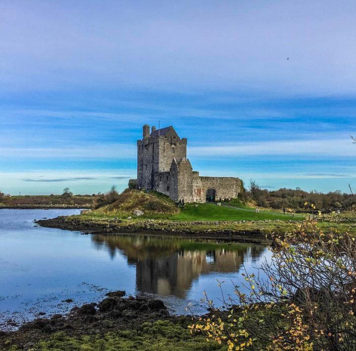 Castelli d'Irlanda: Dunguaire Castle in un'immagine frontale che ne coglie la figura frontale e l'ansa circondata dall'oceano su cui sorge