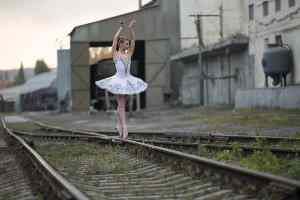 Ballerina posing on the intersection of railway rails. Choosing KPIs to keep your organisation on the rails is boring but critical