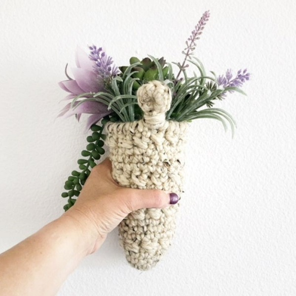 a photo of a hand holding a hanging cone shaped plant hanger showing the reverse side with sturdy hanger.