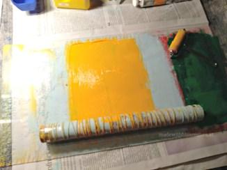Rolle mit Wollfäden und gelber Acrylfarbe