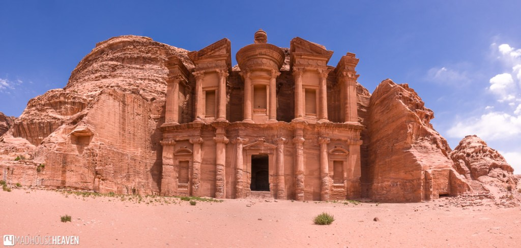 The rose red facade of the Monastery against the bright blue of the afternoon sun in Petra