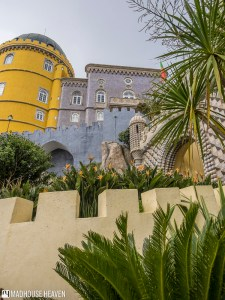 Different levels of the Pena National Palace, fortress walls and palm trees in front