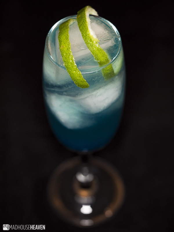 top shot, champagne glass, large ice cubes, lime twist, refreshing cool blue curacao cocktail