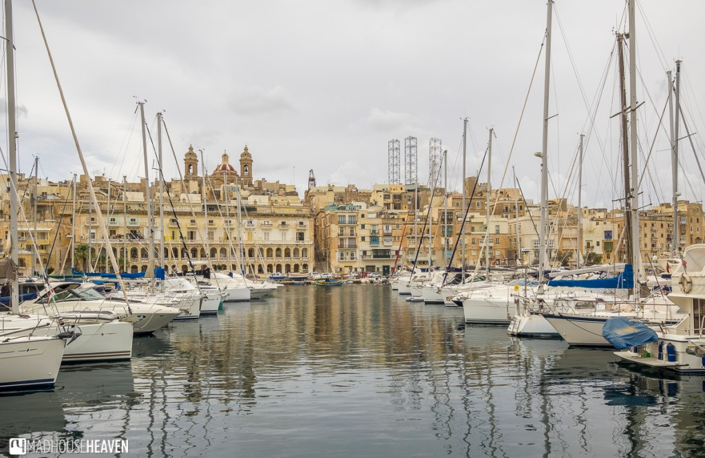 Medieval harbour of Birgu filled with white yachts, the city rising up on a slope in background