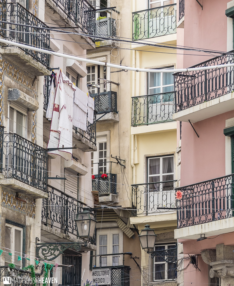 Tightly packed french balconies at crazy angles to each other with criss-crossing wires, Lisbon's Architectural History