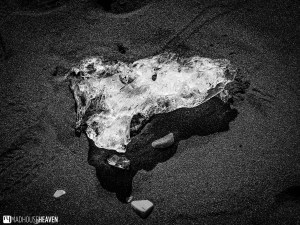 Black and white image of a diamond like piece of ice on the black sands of the Jökulsárlón Glacier Lagoon