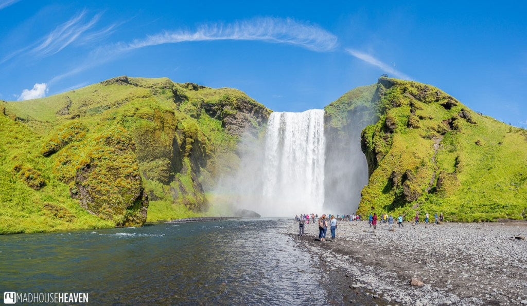 The crowd of tourists is gathered in front of the Skógafoss waterfall in Iceland
