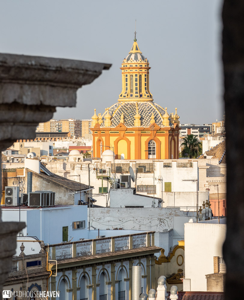 A blue and white striped dome of Iglesia de Santa Cruz as seen from the Seville Cathedral